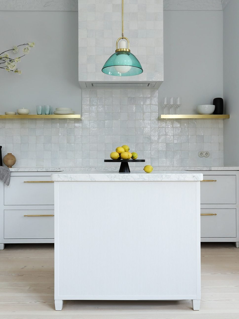 white kitchen with blue pendant over the island