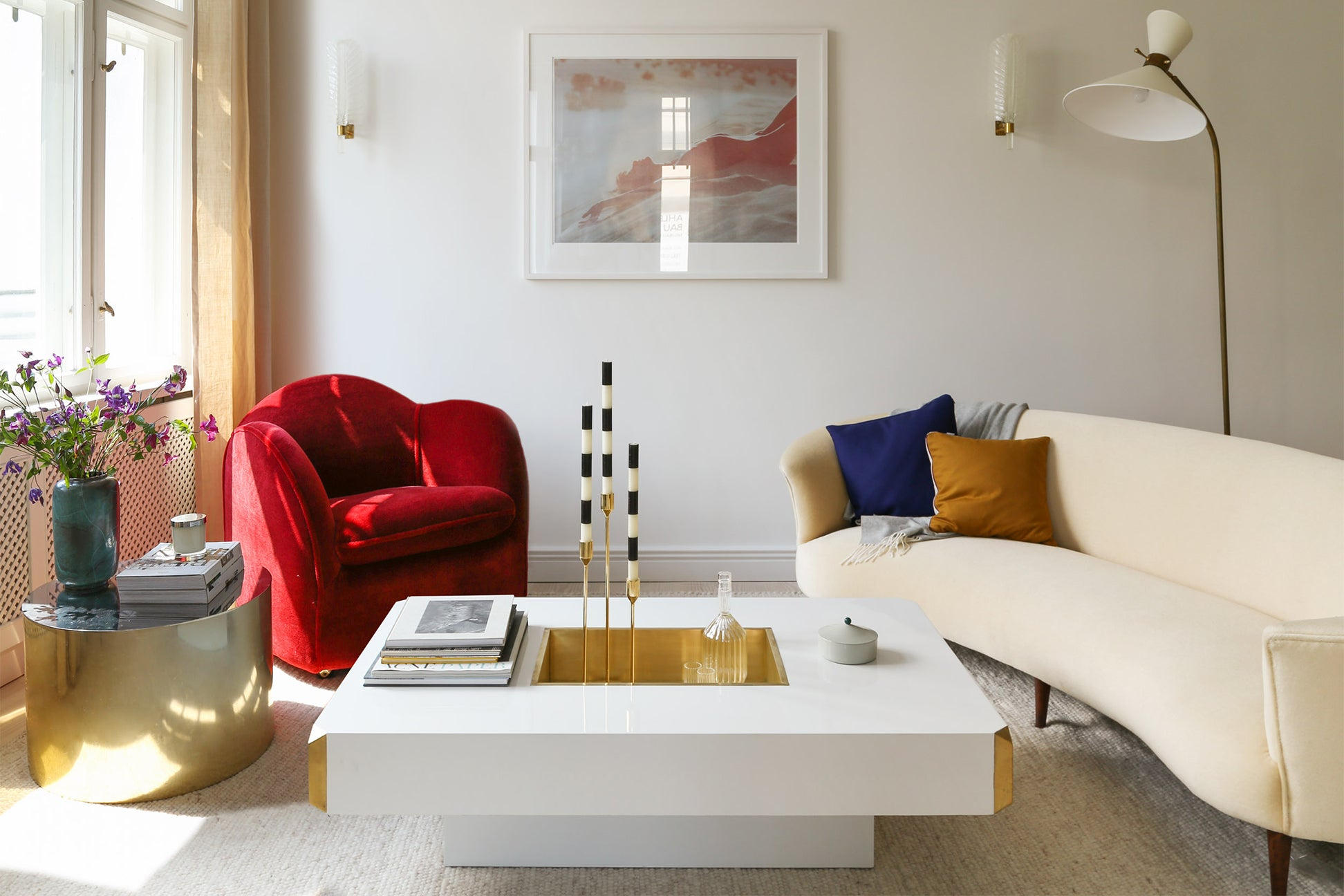 living room with white coffee table red chair and white sofa
