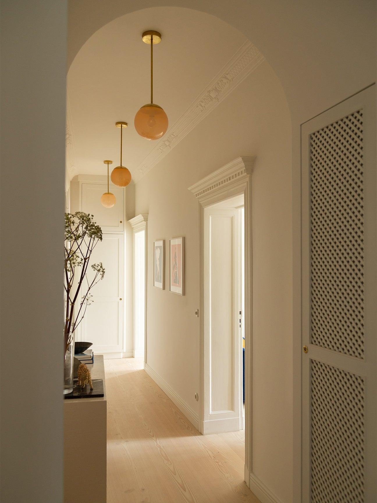 hallway with pink globe pendants