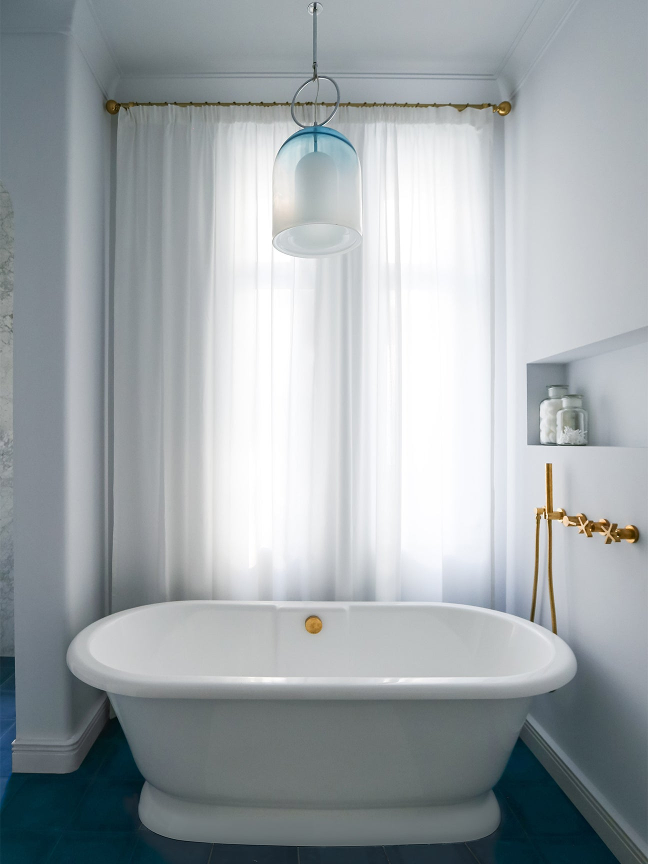 white bathtub in front of curtain window