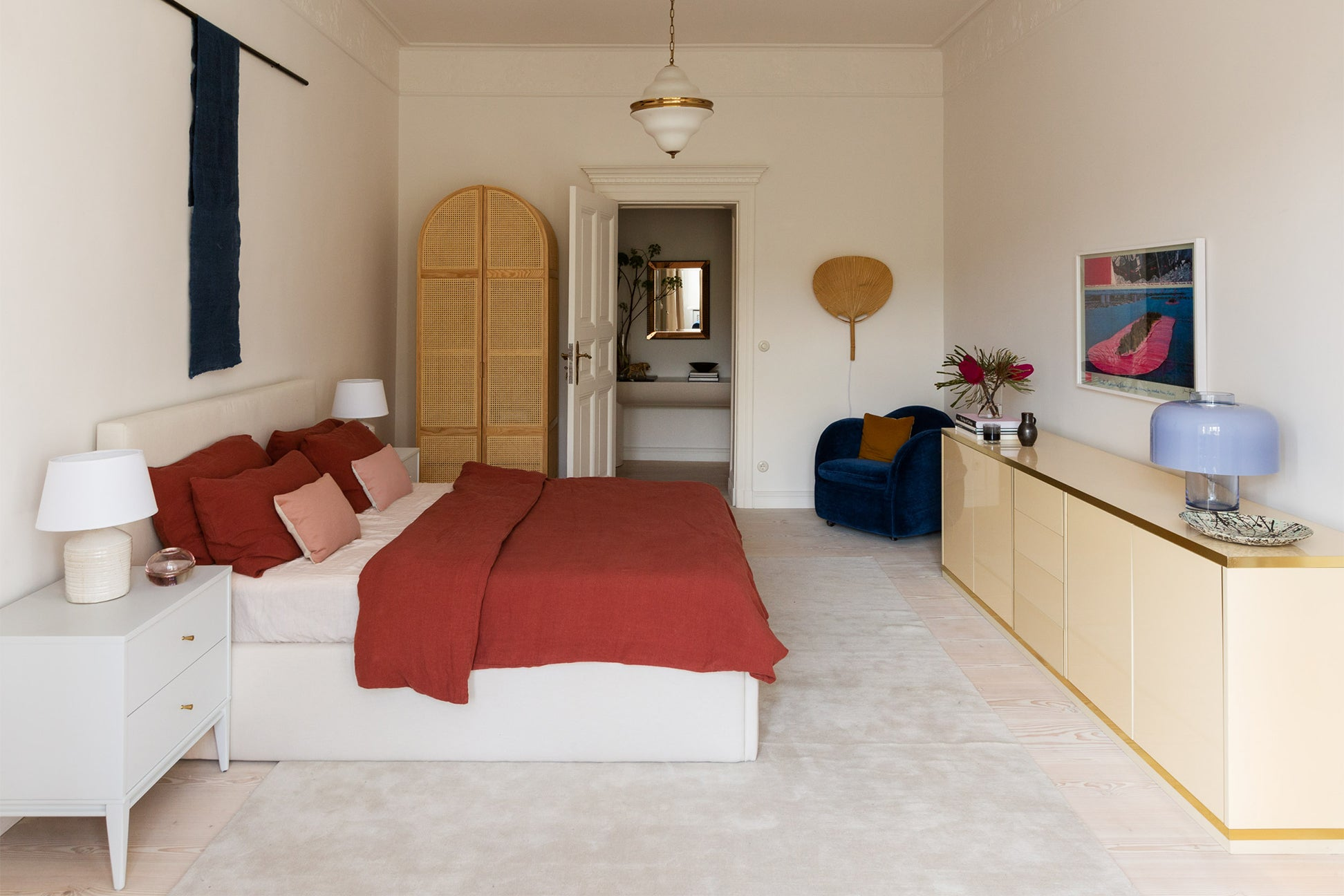 bedroom with red bedding lacquer credenza and cane wardrobe