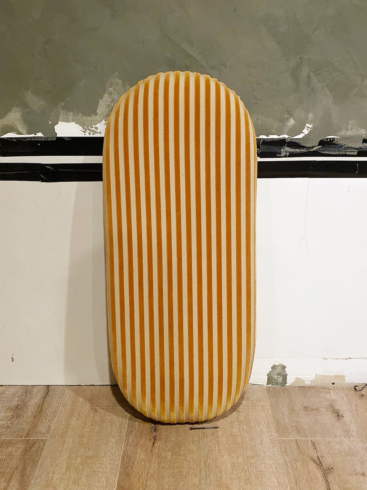 oval board covered in striped fabric