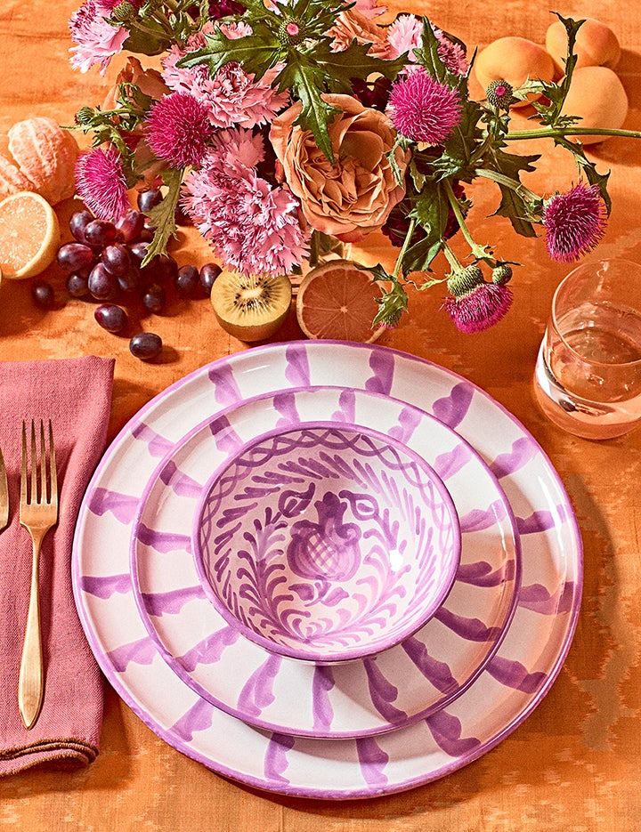 purple ceramic plate on table with floral arrangement