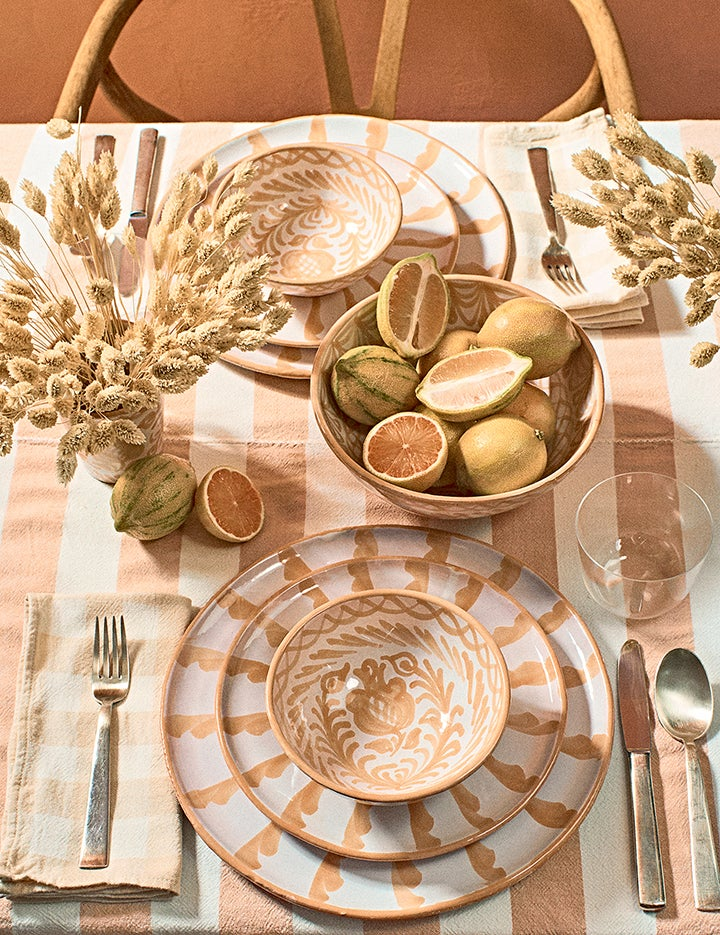 neutral tabletop with ceramic plates and bowls and floral arrangement and fruit
