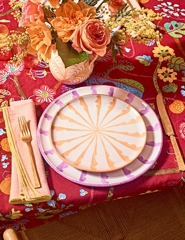 two ceramic plates on red floral tablecloth
