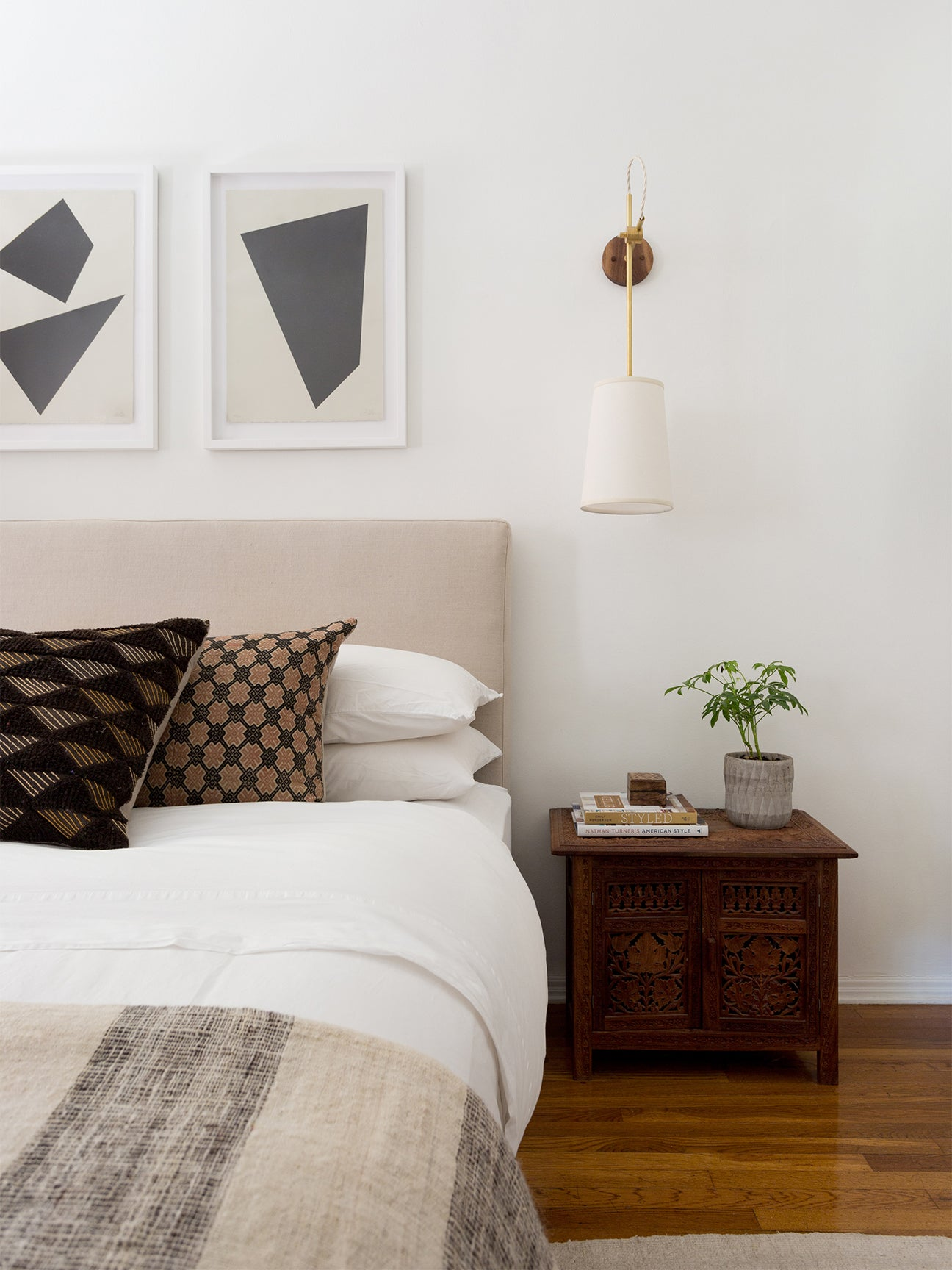 Bed with neutral blanket and headboard