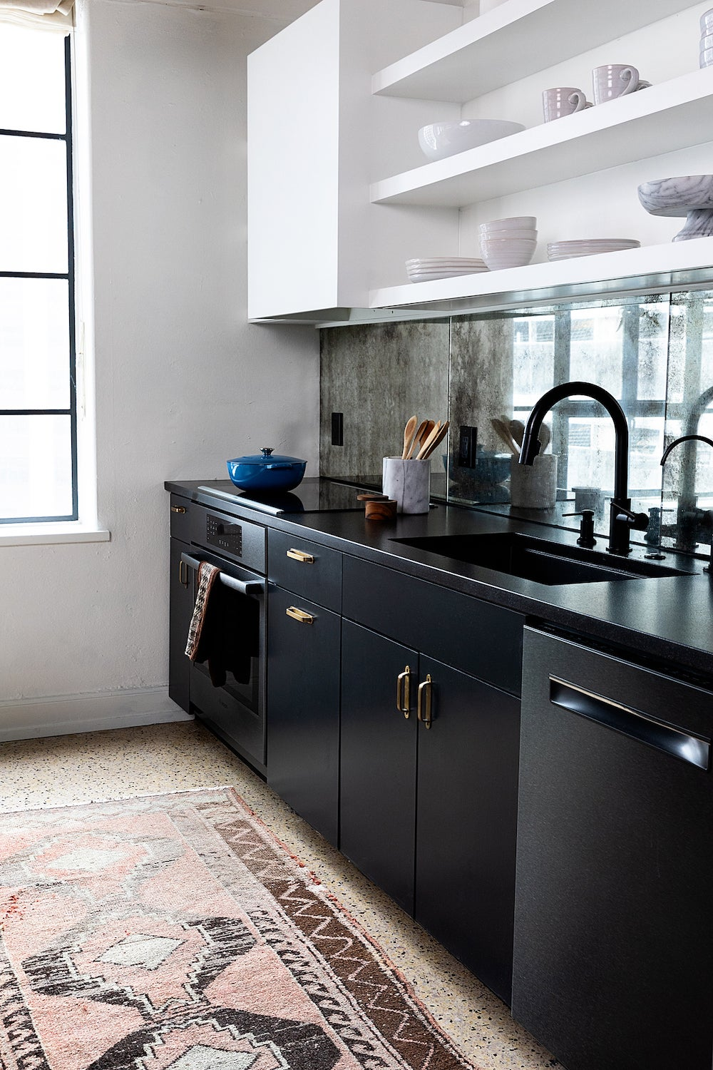black lower cabinets and patina mirror backsplahs