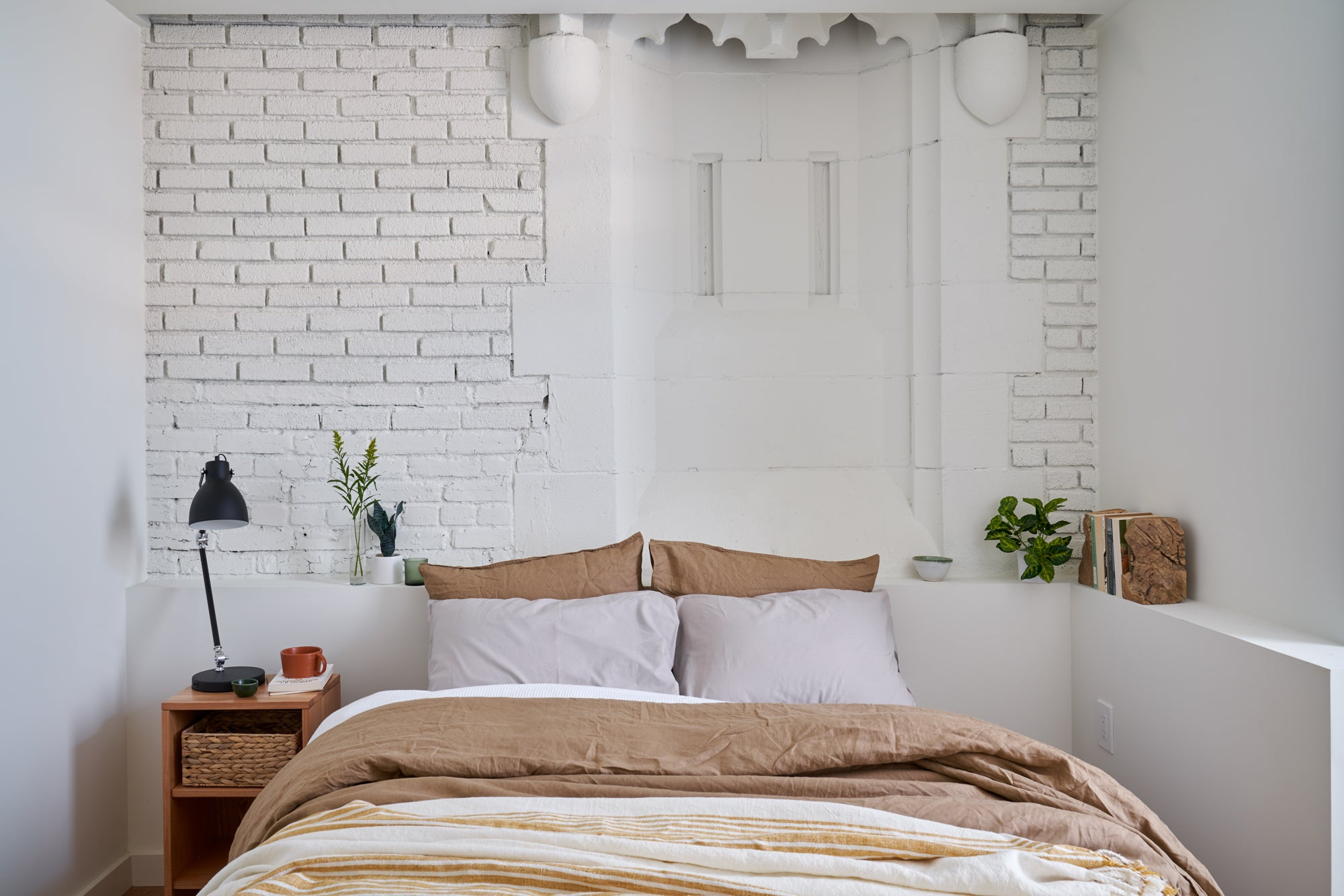bedroom with white brick walls and church niche