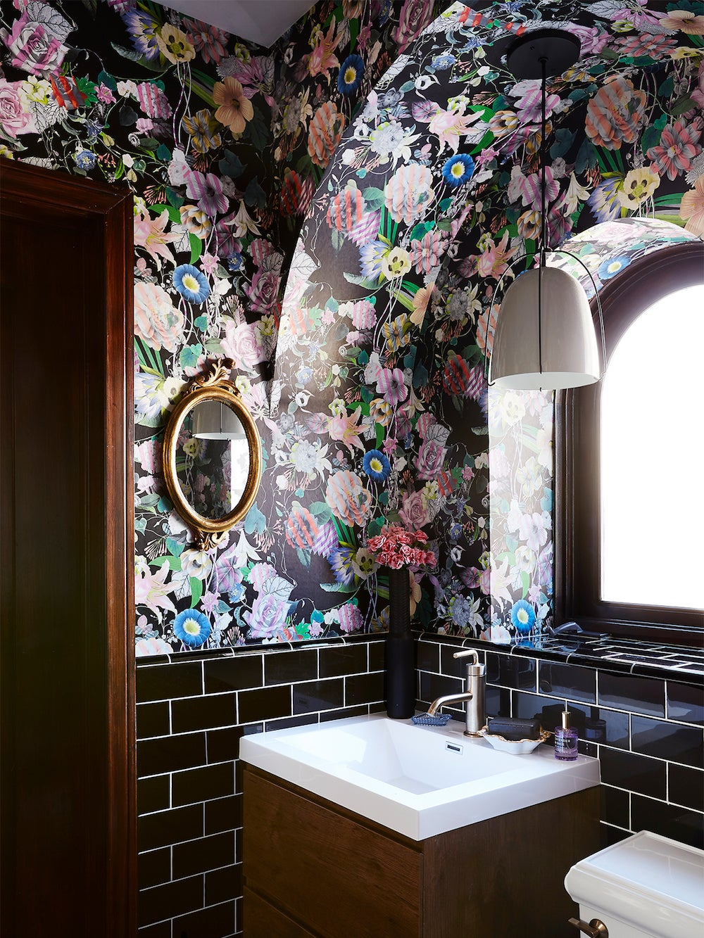 arched bathroom with black floral wallpaper