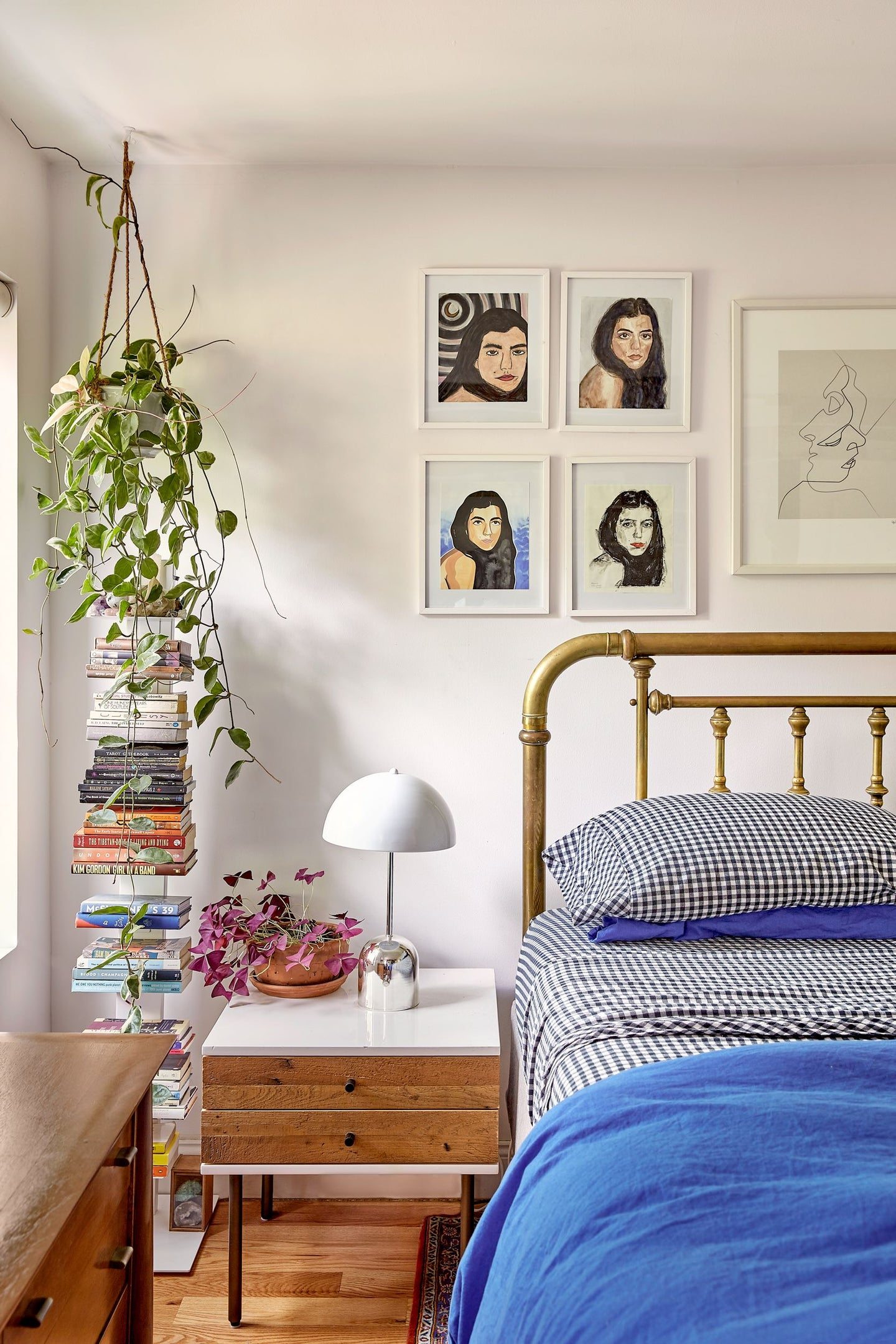 Bedroom with hanging plant and stack of books