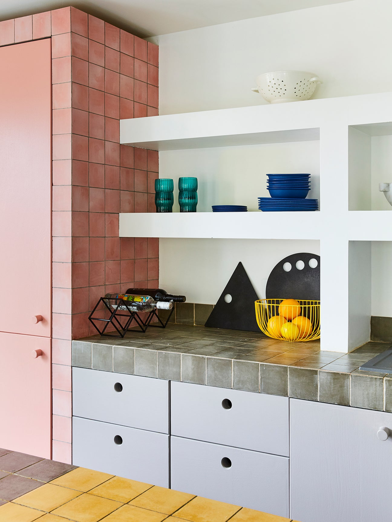 kitchen corner with white shelving and pink cabinet