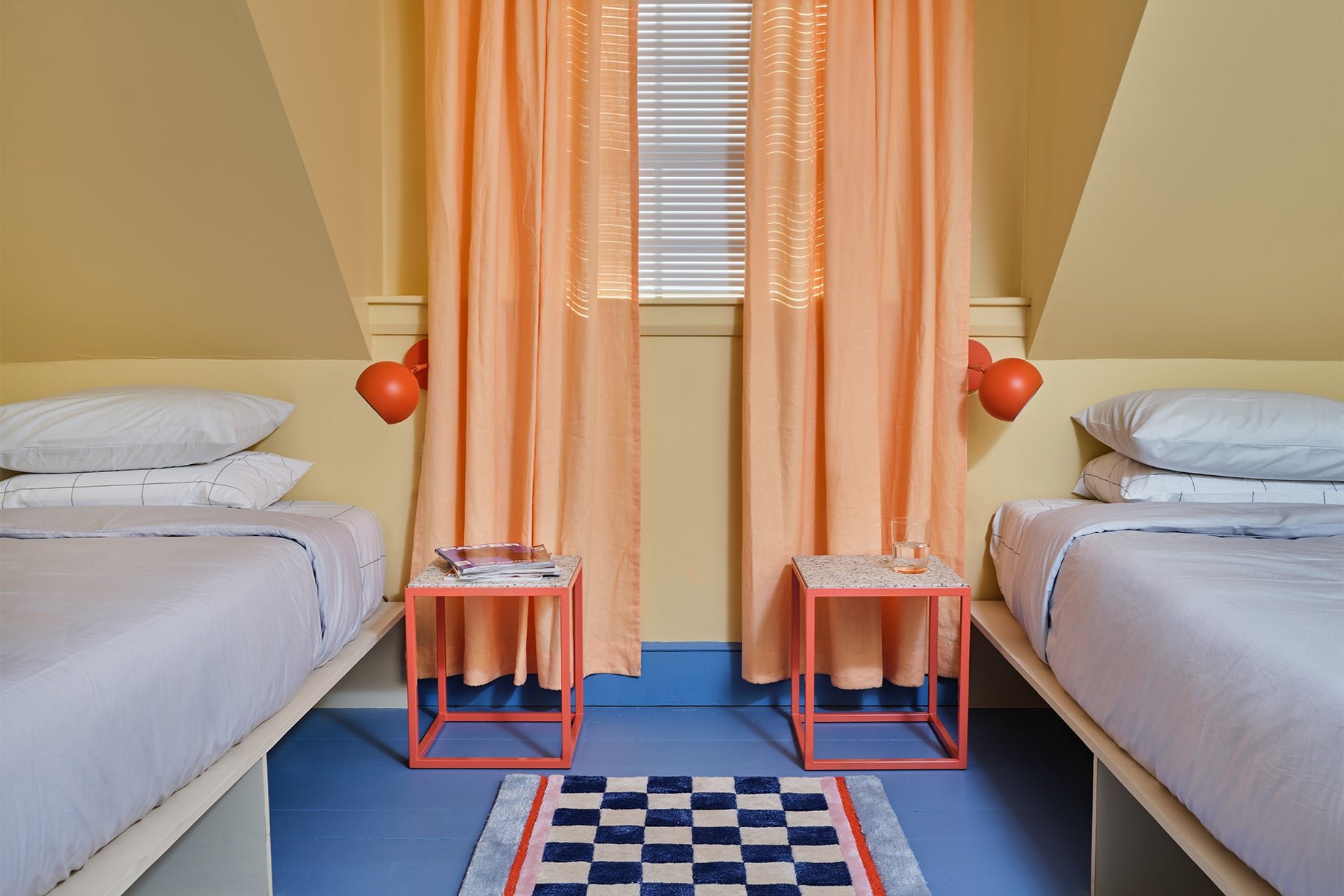 Room with yellow walls and twin blue beds