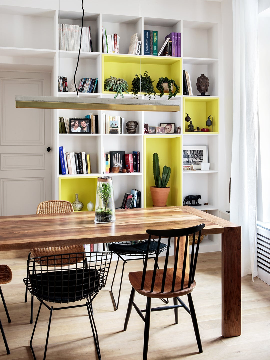 yellow and white painted bookcase wall in dining room