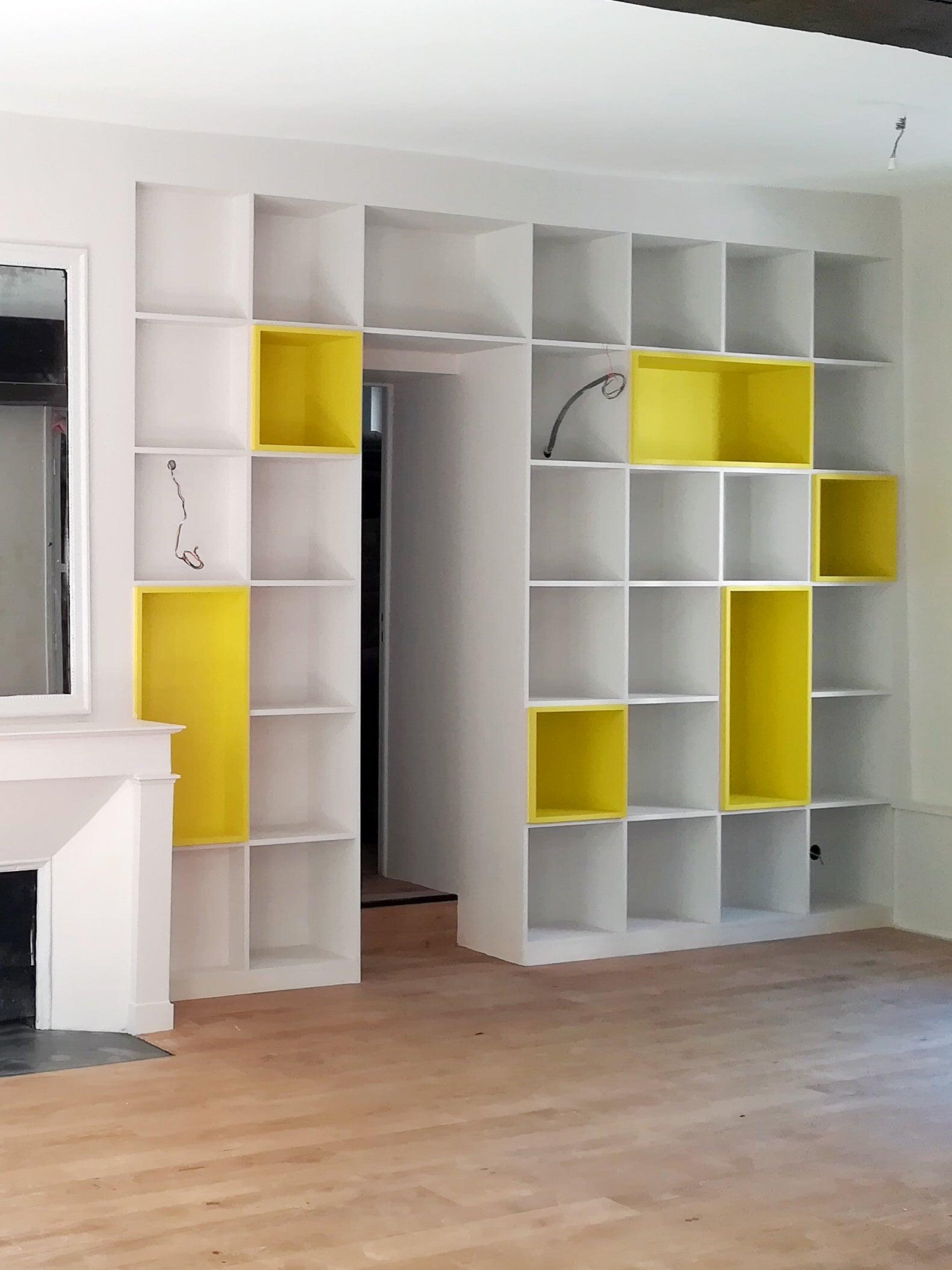 yellow and white floor to ceiling bookshelf