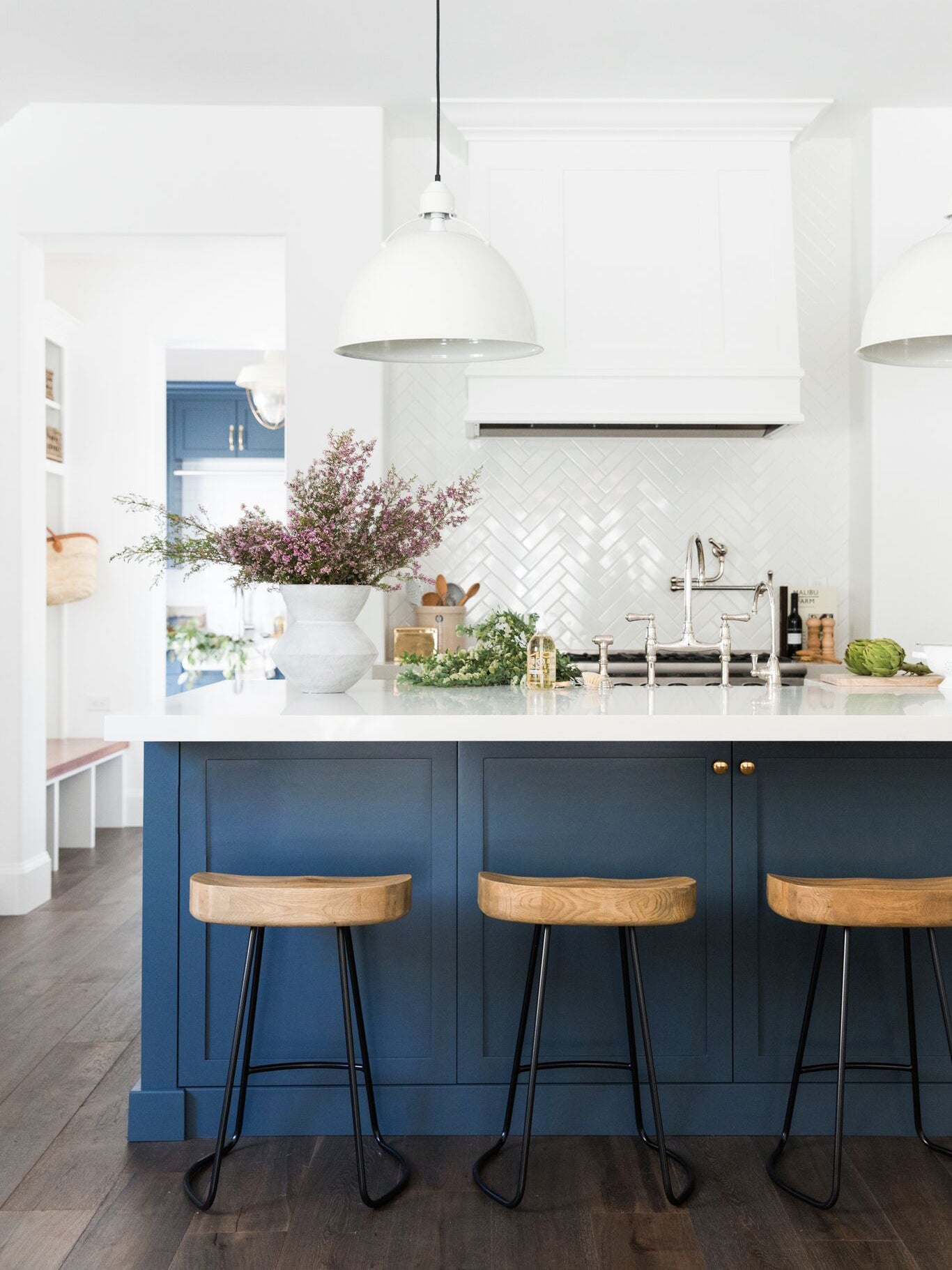 navy blue kitchen island with bar stools near by
