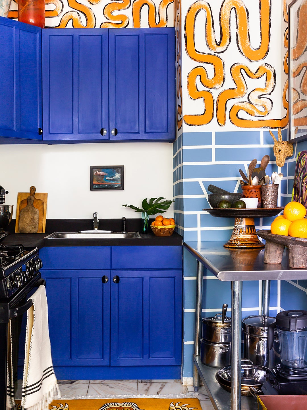 royal blue kitchen cabinets with orange mural