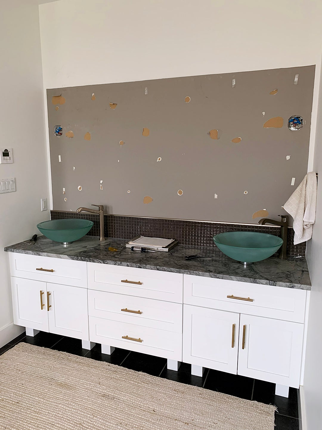 exposed drywall and blue sinks
