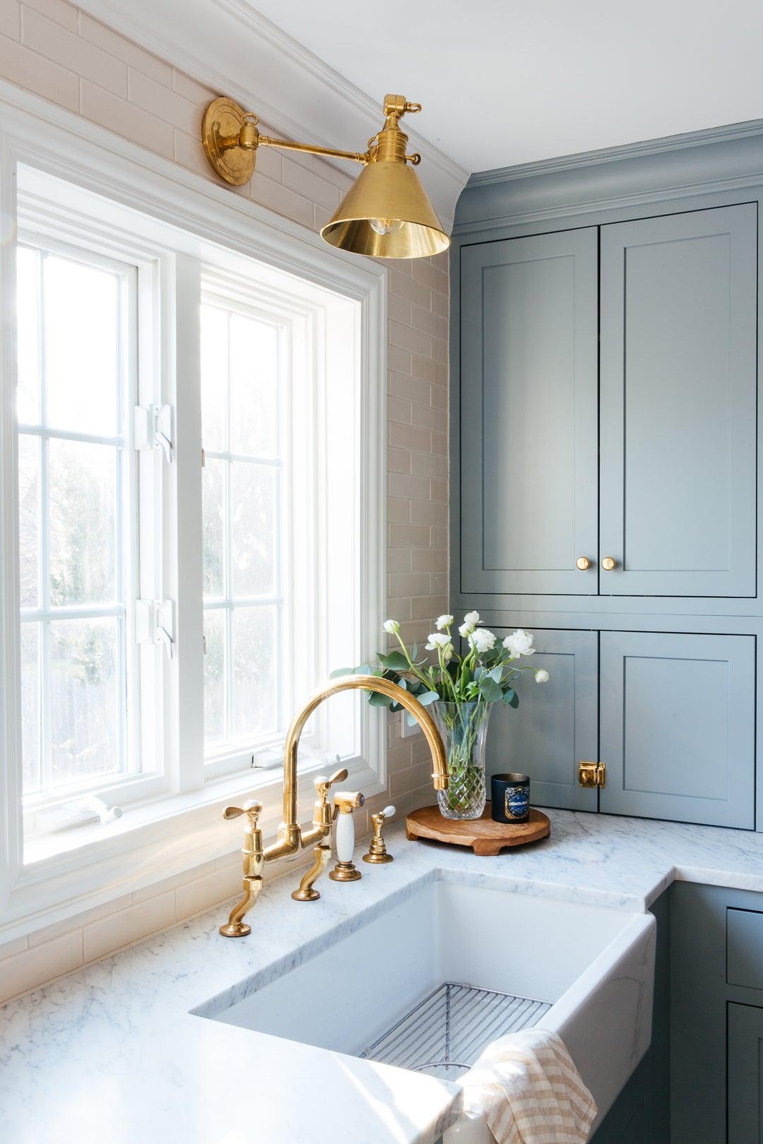 Kitchen sink next to blue cupboard