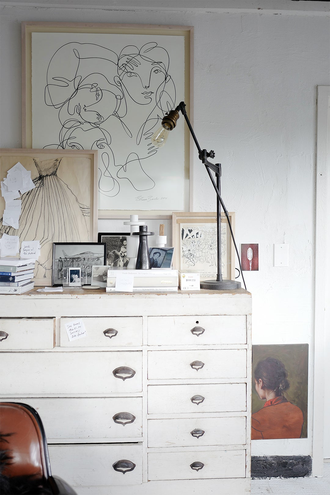 white cabinet with art and sticky notes