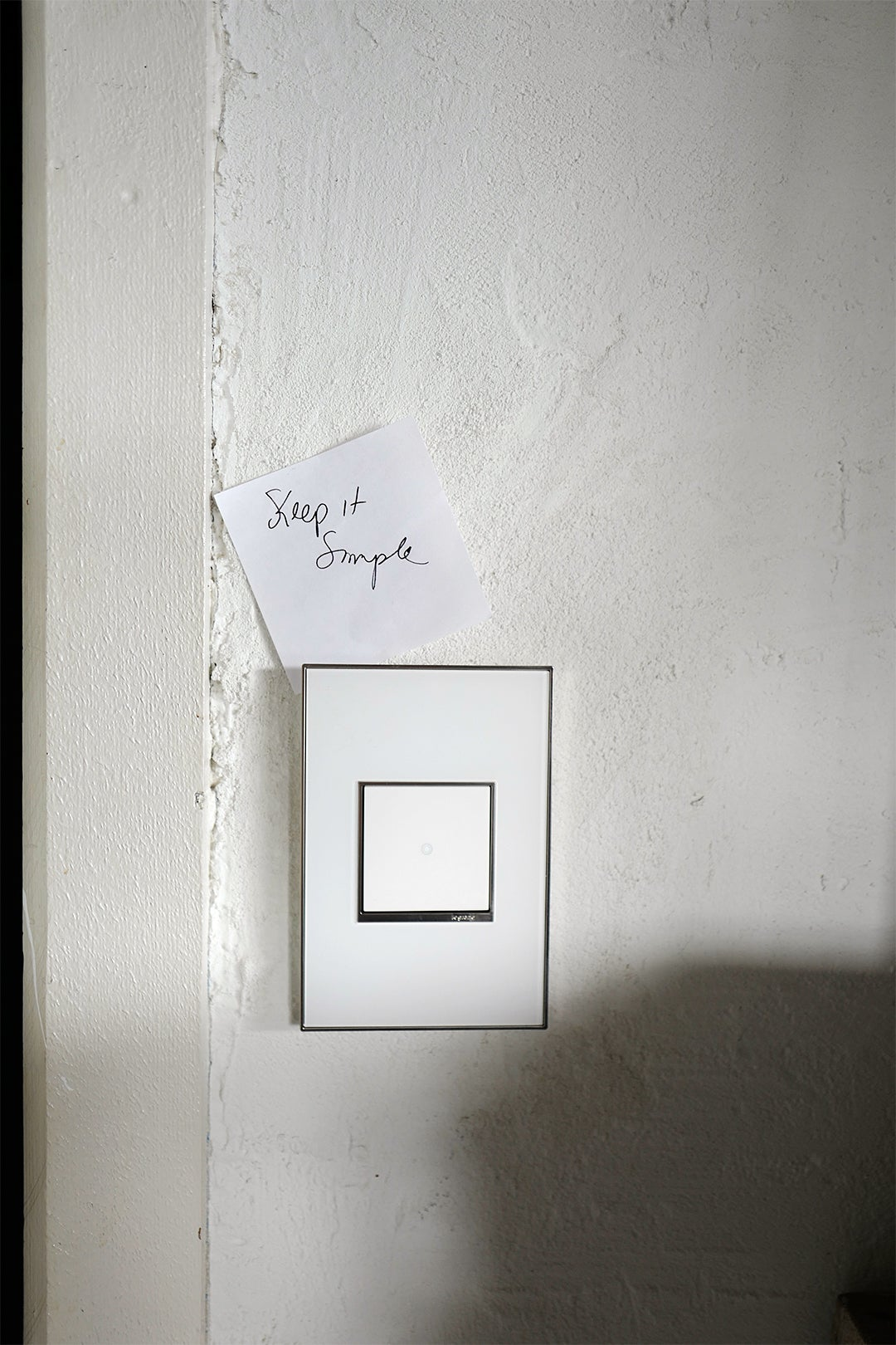 white light switch with note stuck to it