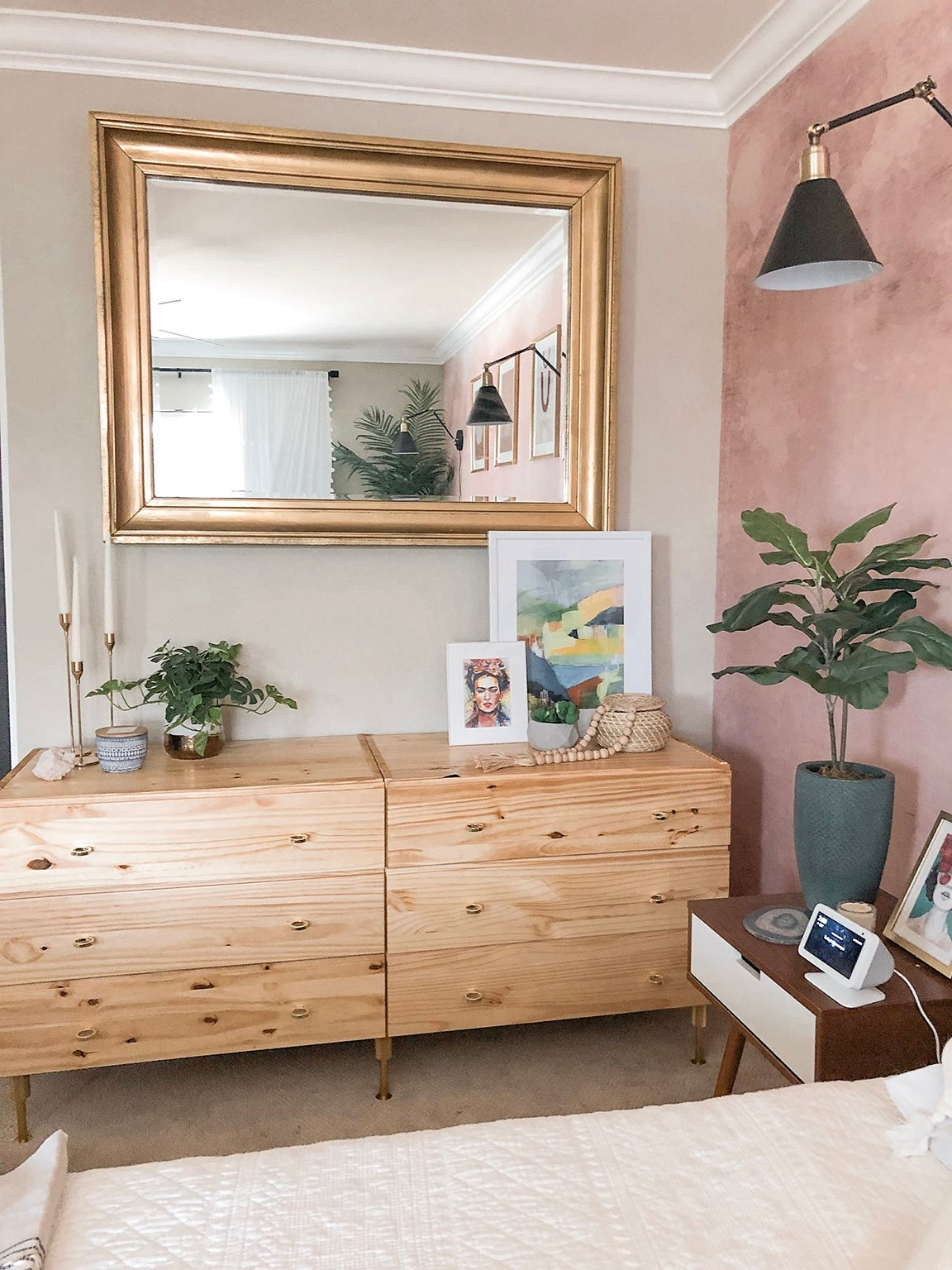 wood dresser with large brass mirror and pink walls