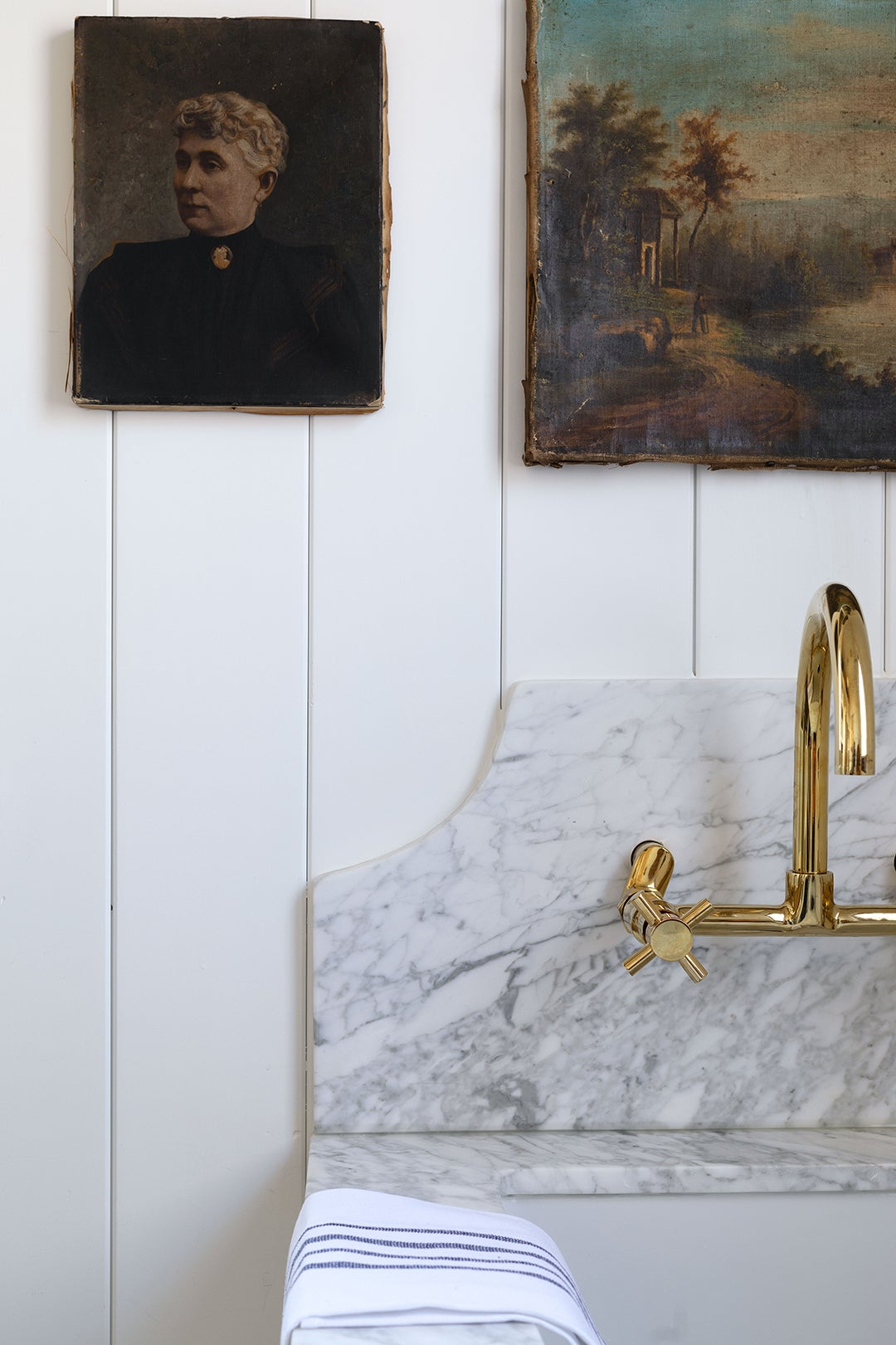 marble curved backsplash with brass faucet
