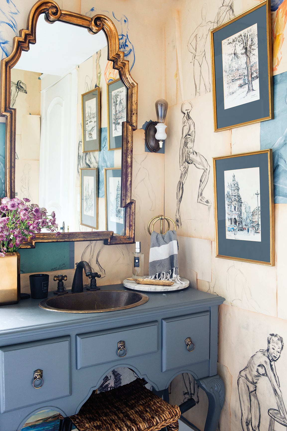 blue powder room with sketches hung on the wall
