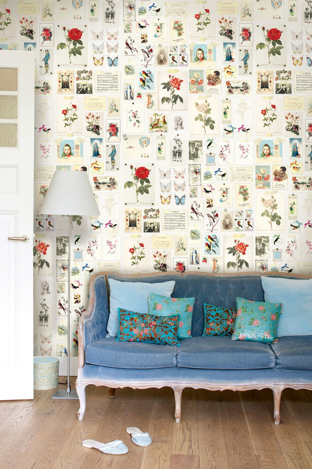 blue sofa in front of floral print wallpaper
