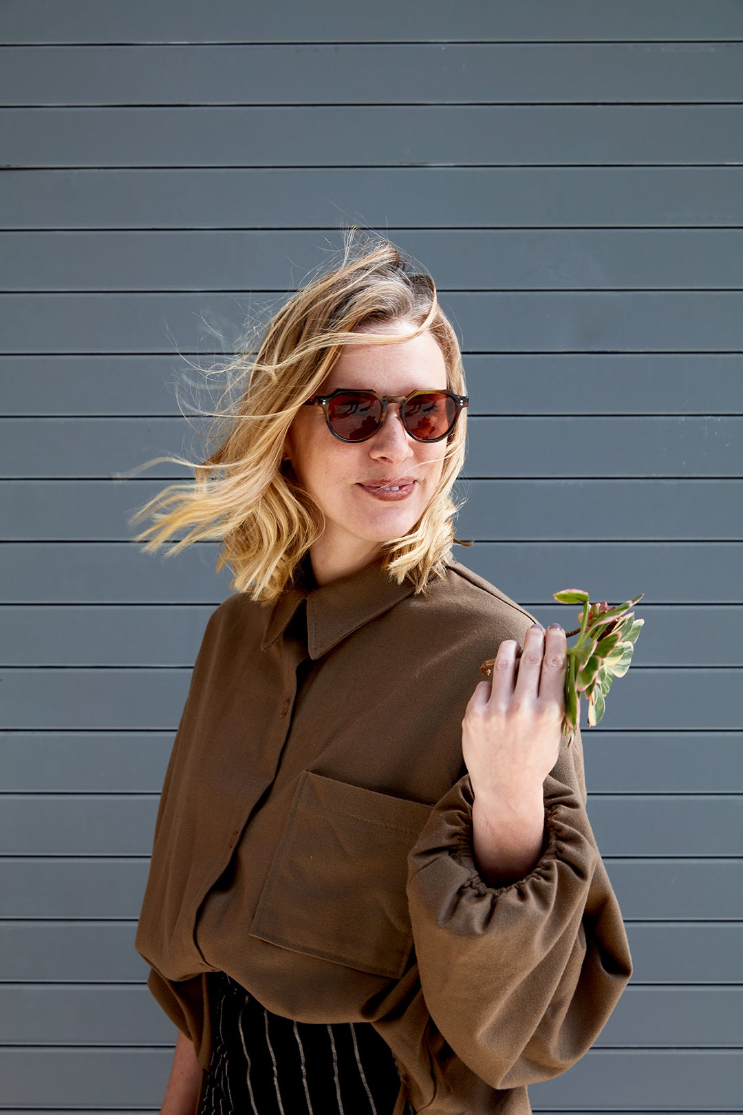 woman with sunglasses holding leaf