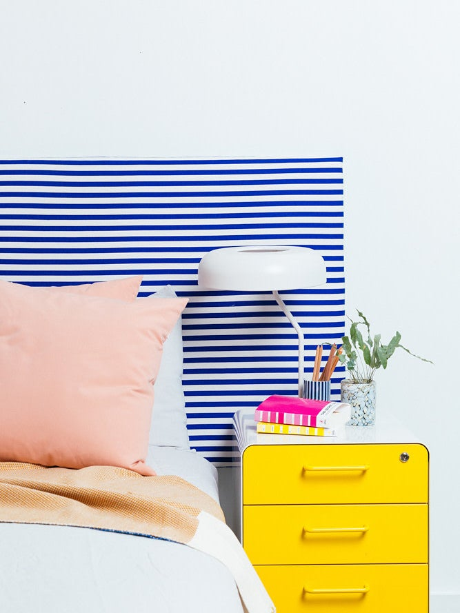 striped blue and white headboard and yellow nightstand
