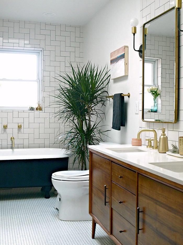Bathroom with black tub and plant