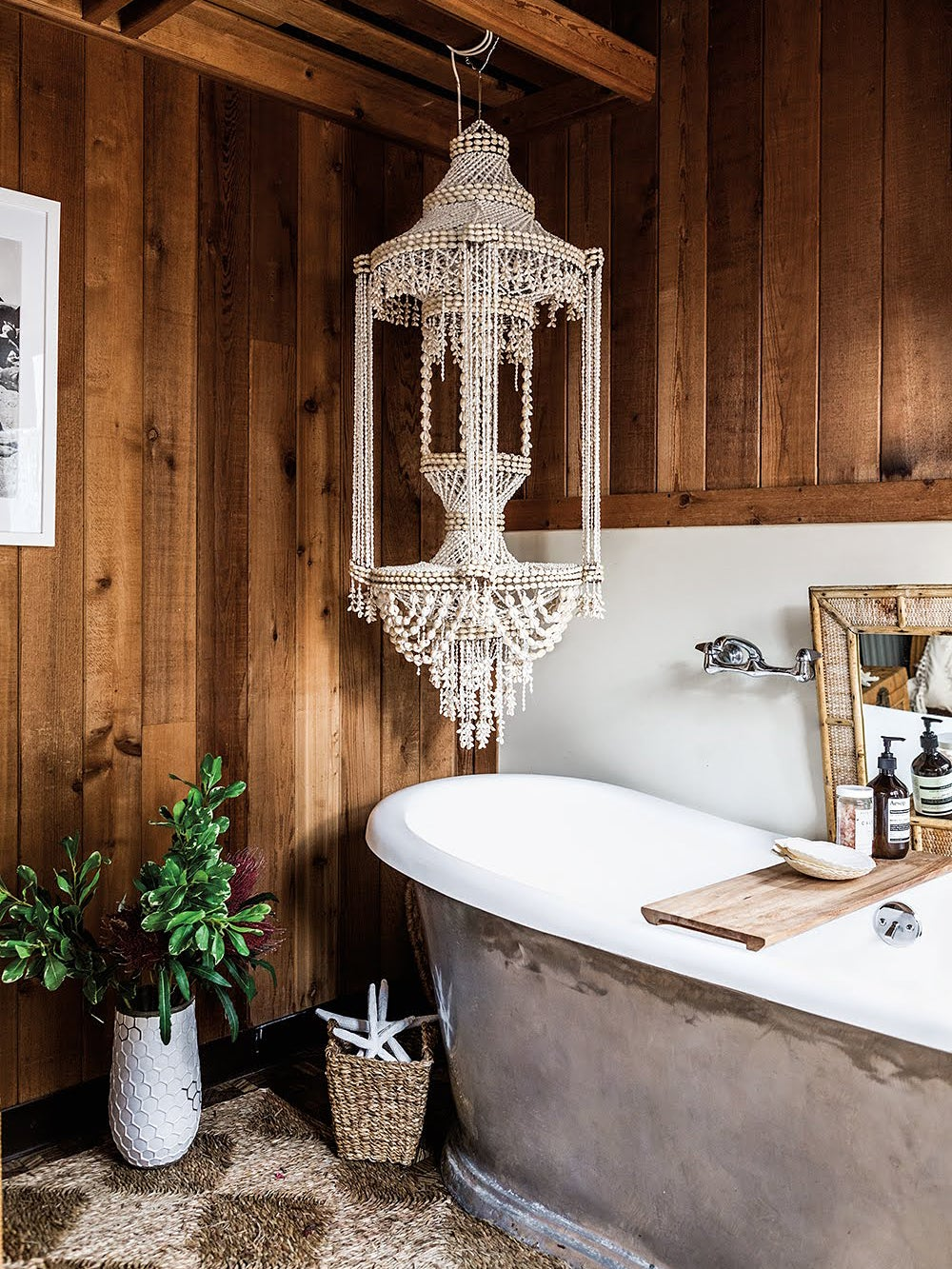 bathtub with elaborate light fixture hanging over it