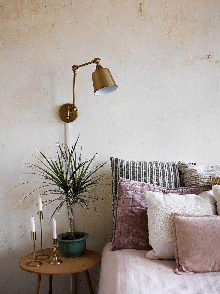 bed with muted pink pillows and brass sconce