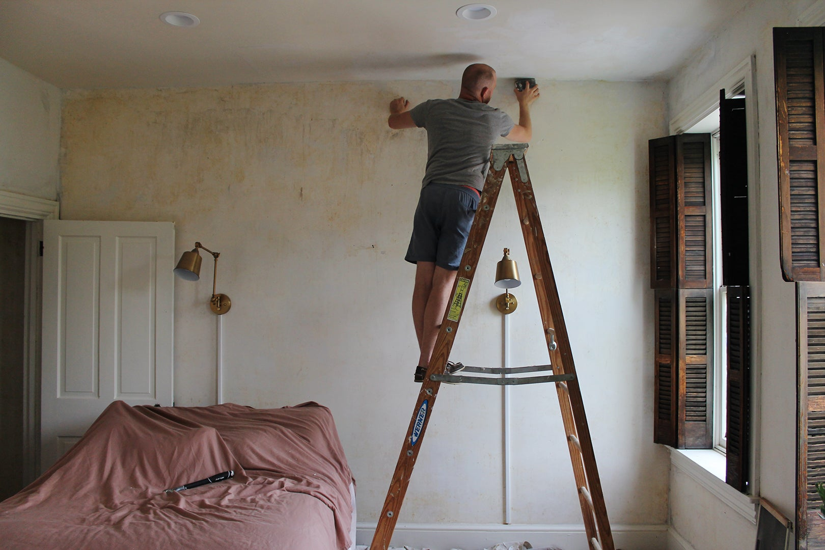 man painting the top of a wall