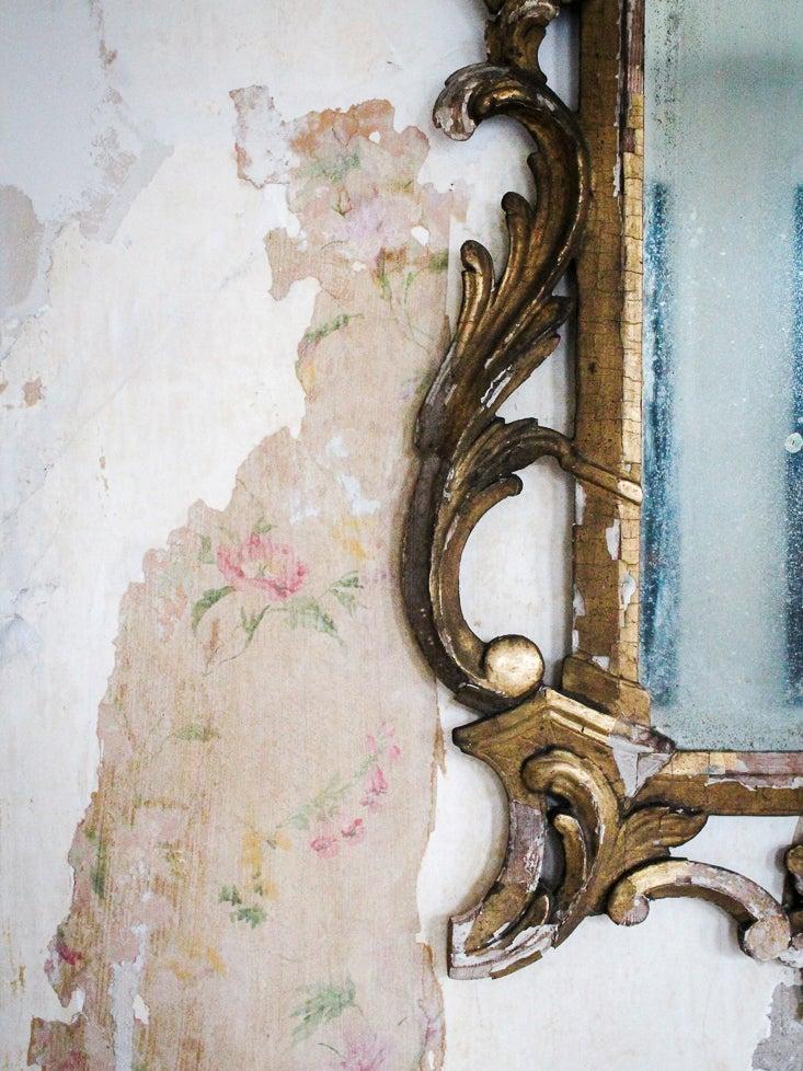 brass mirror with floral wallpaper peeking through