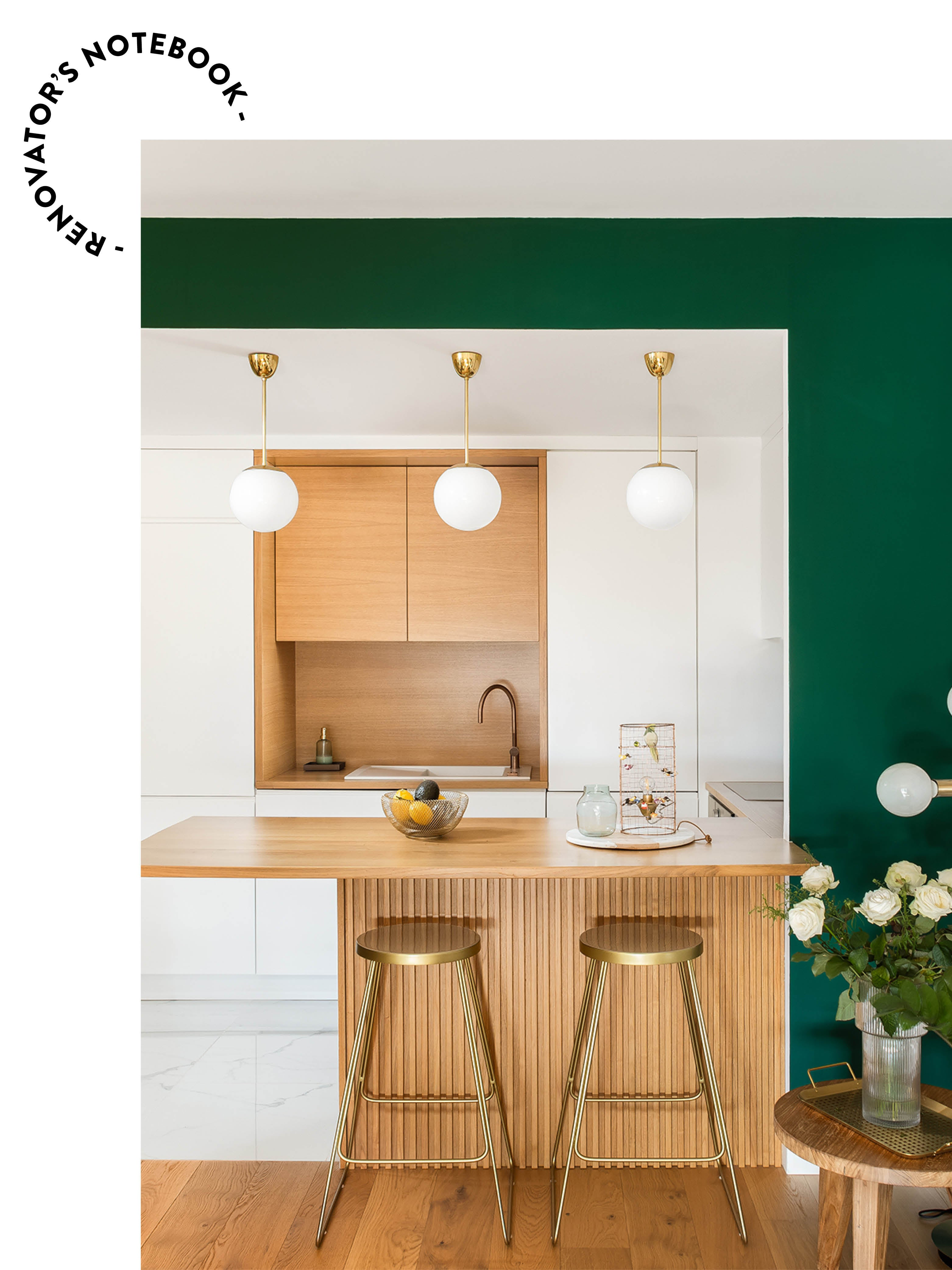 green and white kitchen with pendant lights over island