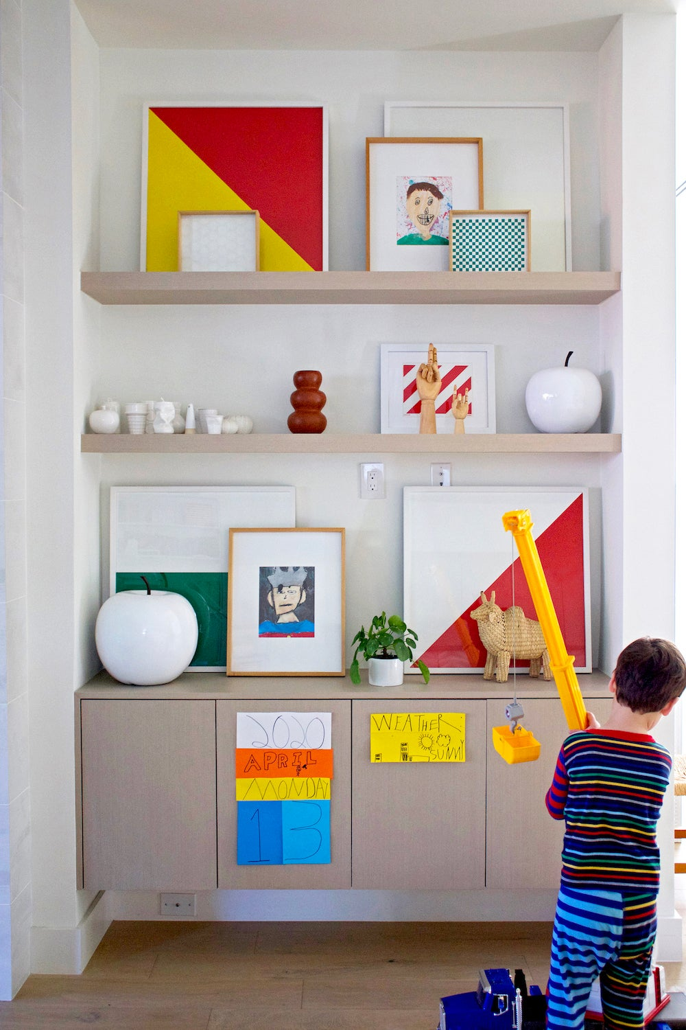 boy playing with toy in front of shelves