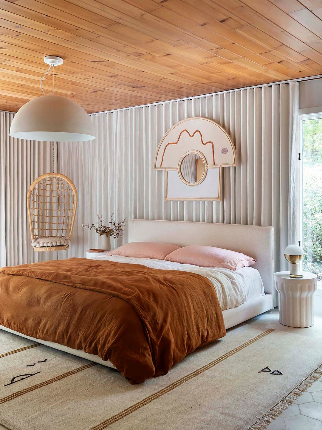pink and orange bed with modern wood ceiling and gray drapes