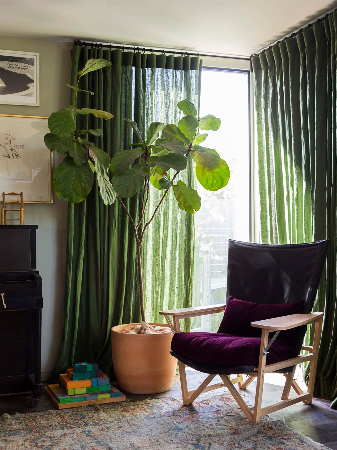 green curtains with a plum chair in a living room
