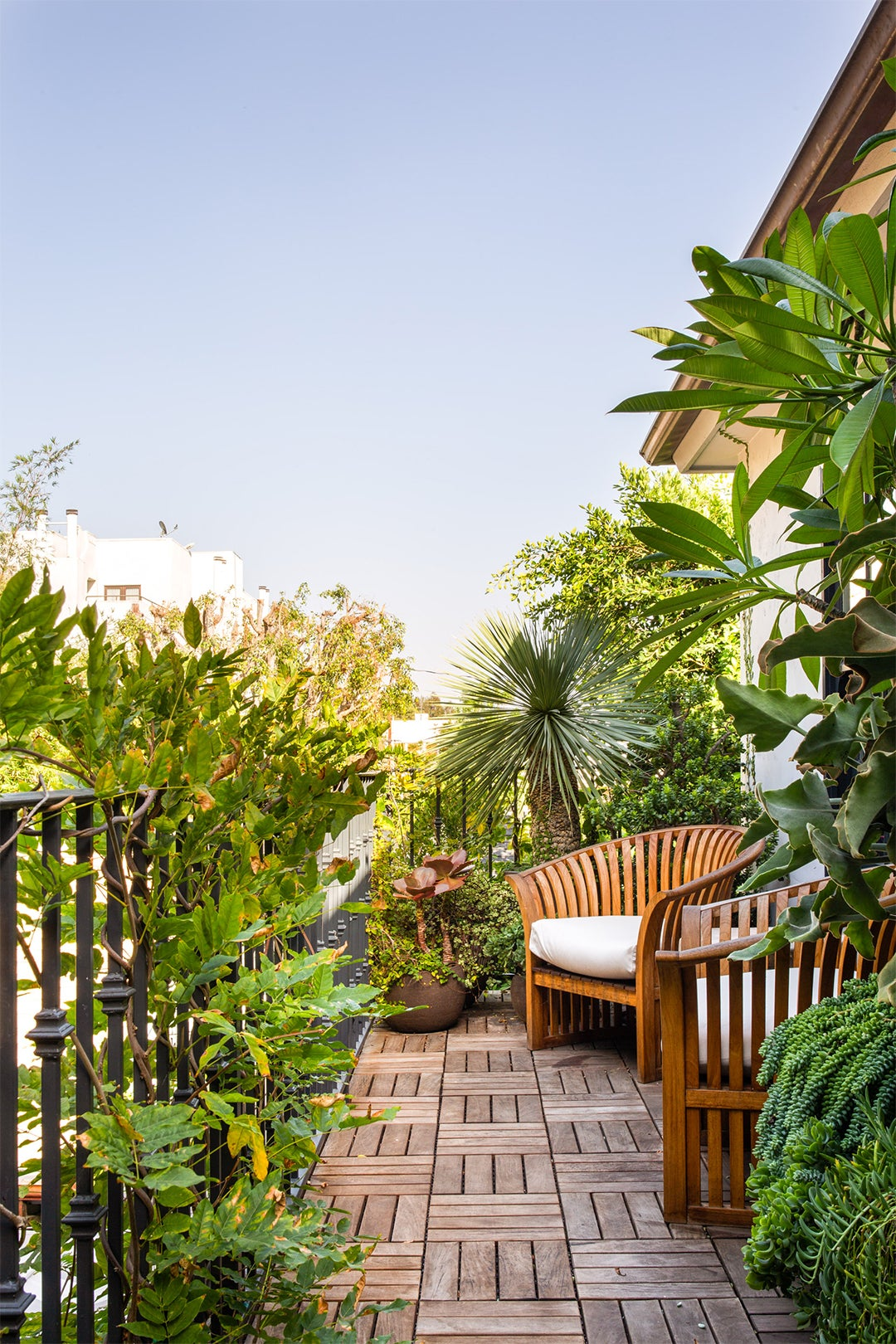 balcony with lots of plants and wooden armchair