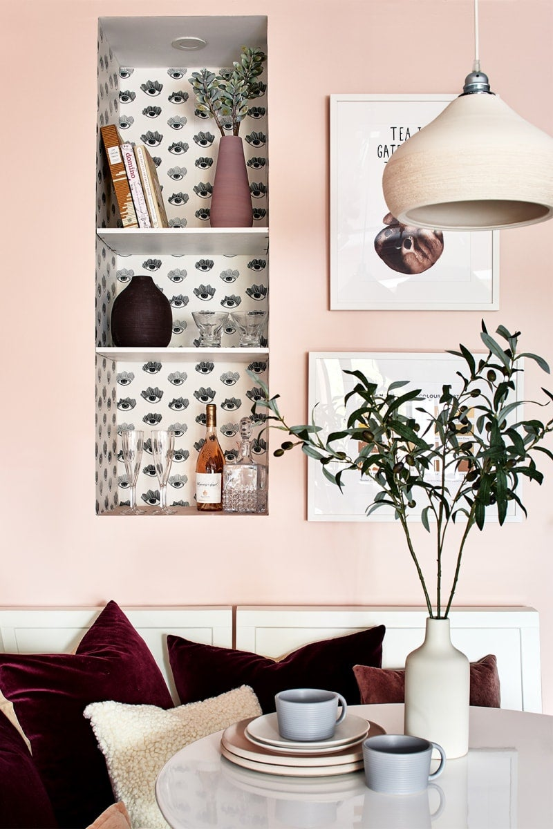 pink breakfast nook with black and white wallpaper shelf
