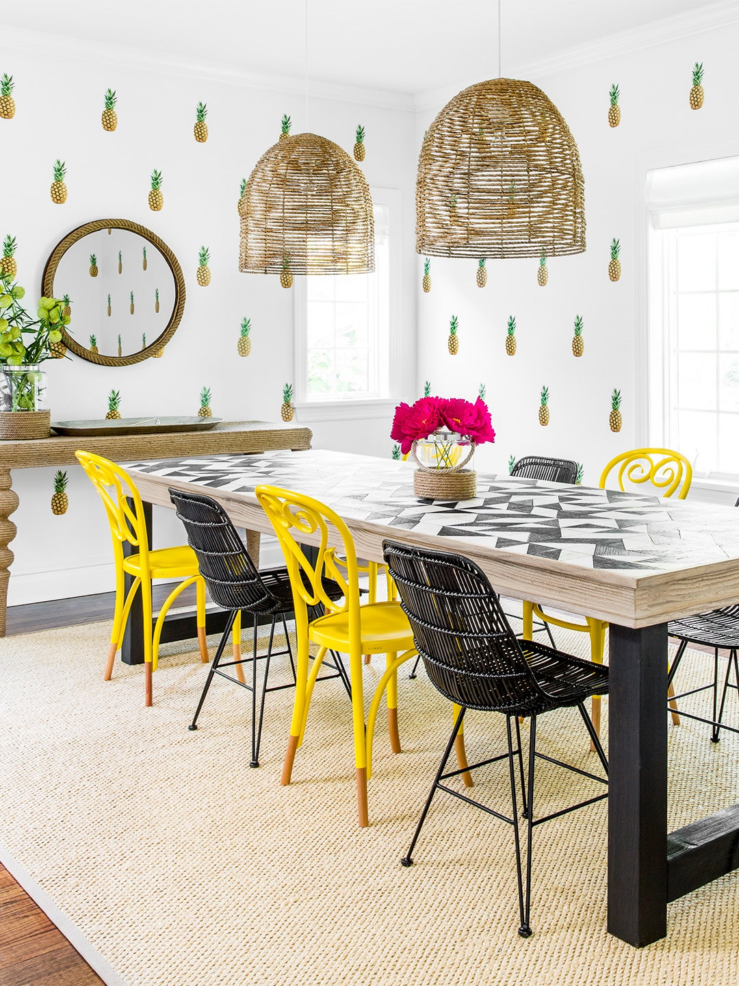 dining room with pineapple decals on wall and yellow chairs