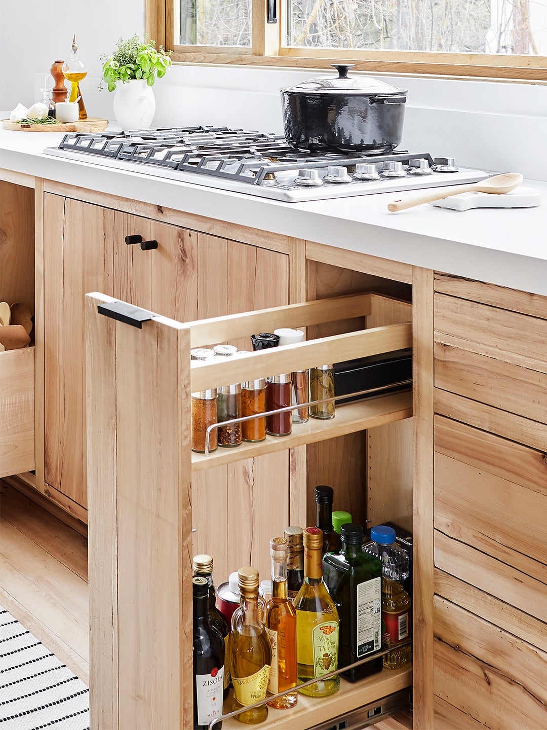 drawer coming out of a cabinet with spices in it