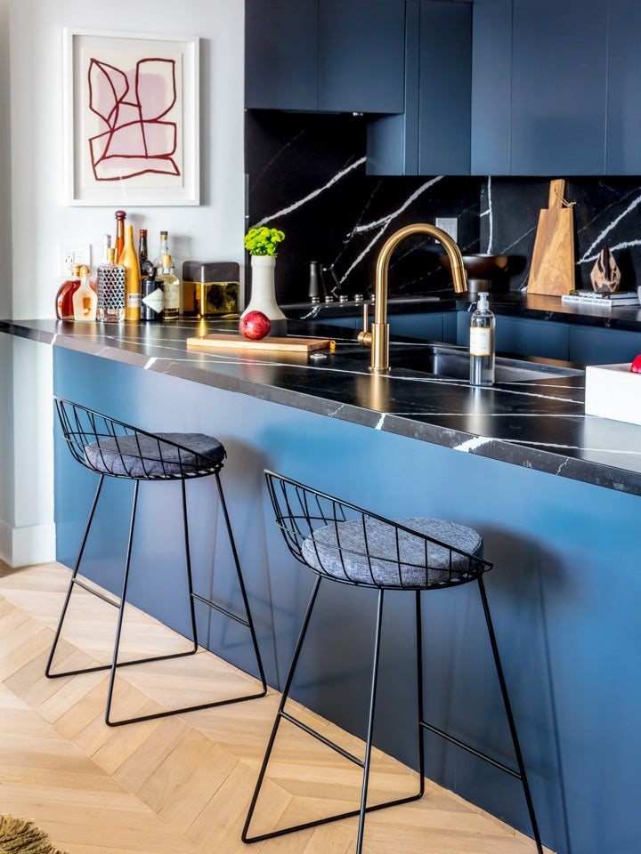 wire barstools at a blue and black countertop