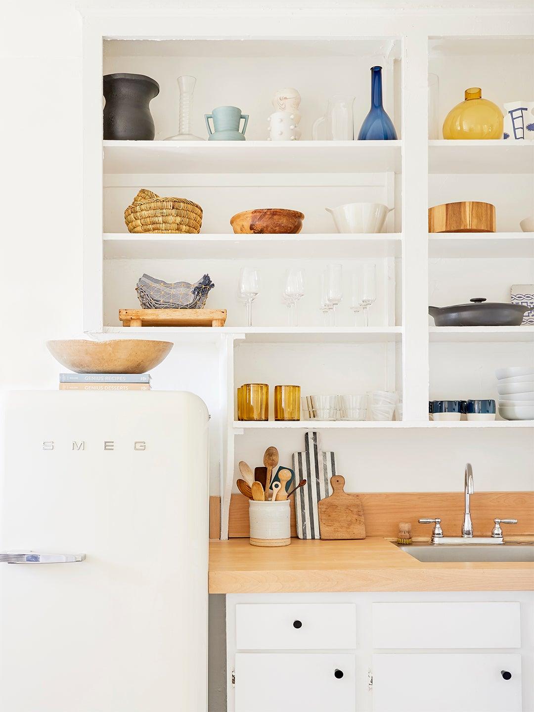 white doorless kitchen cabinets and smeg fridge