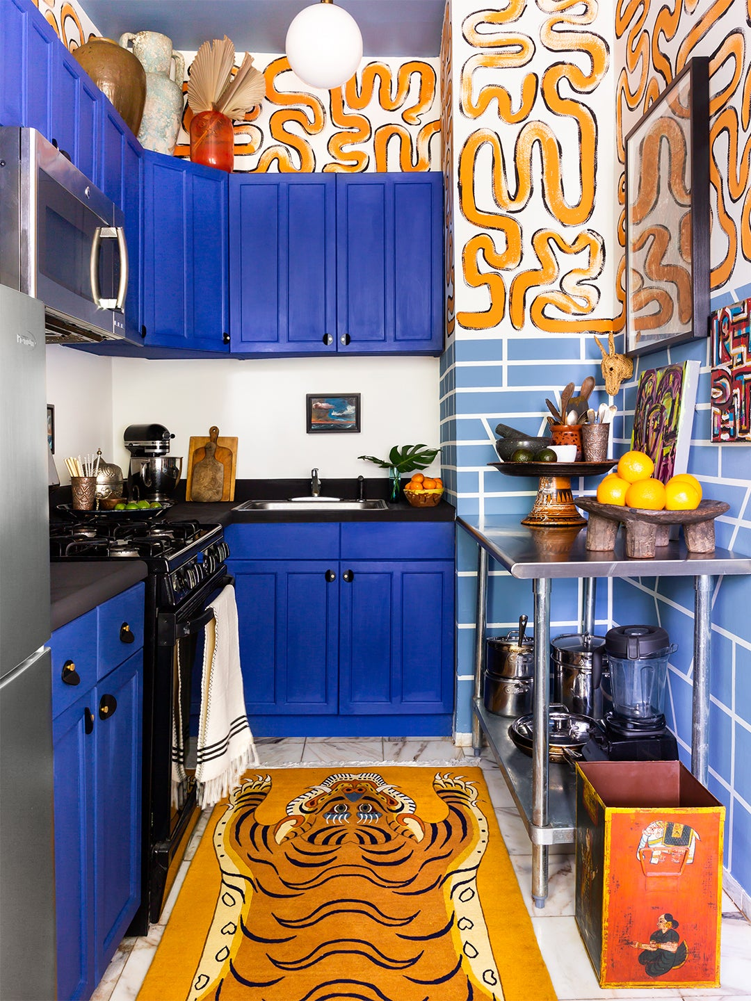 cobalt blue kitchen cabinets with orange wall mural