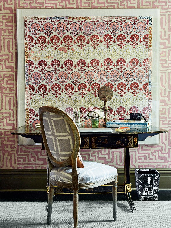 desk in front of pink wallpaper
