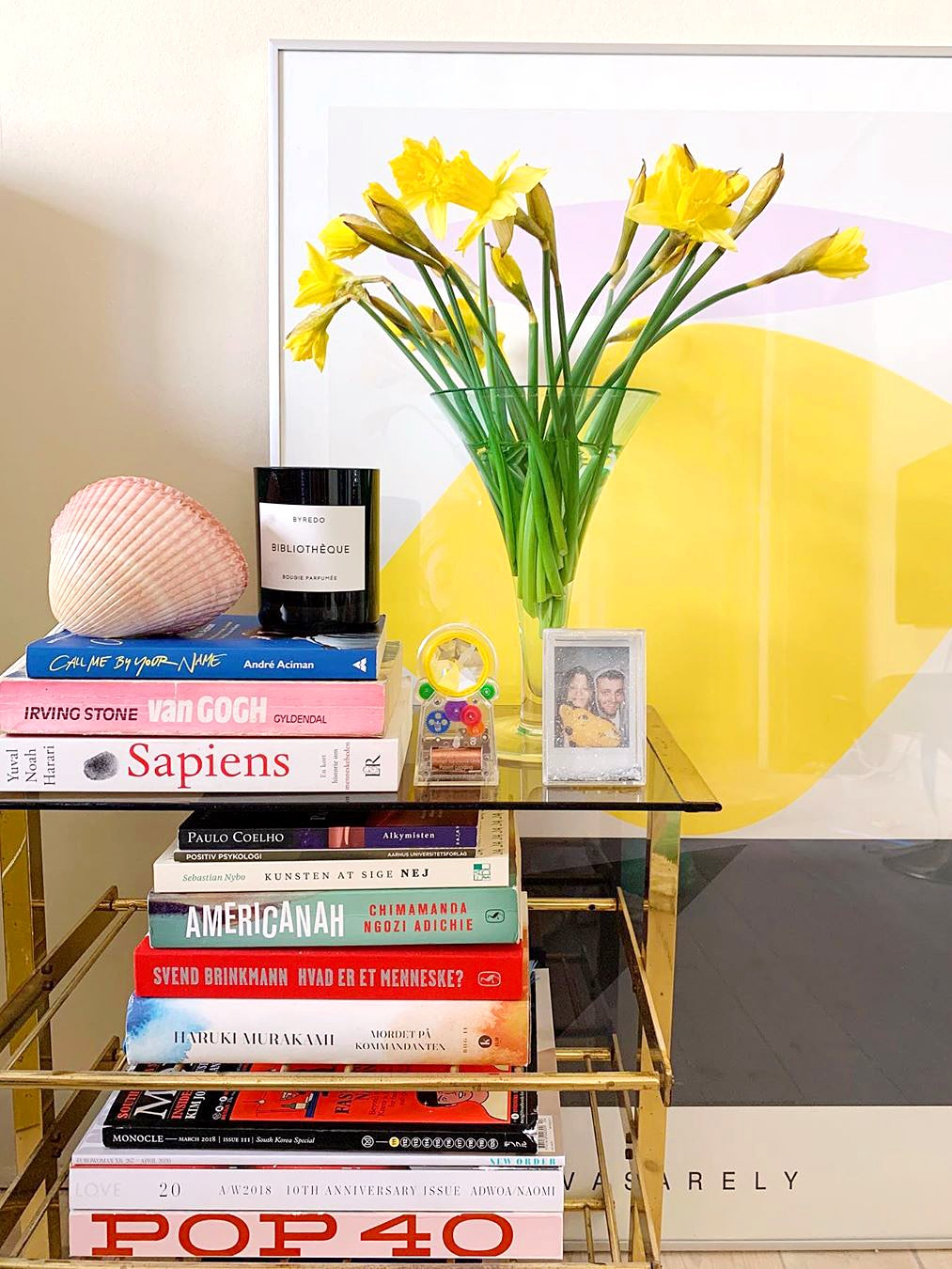 Shelf with colorful books and flowers