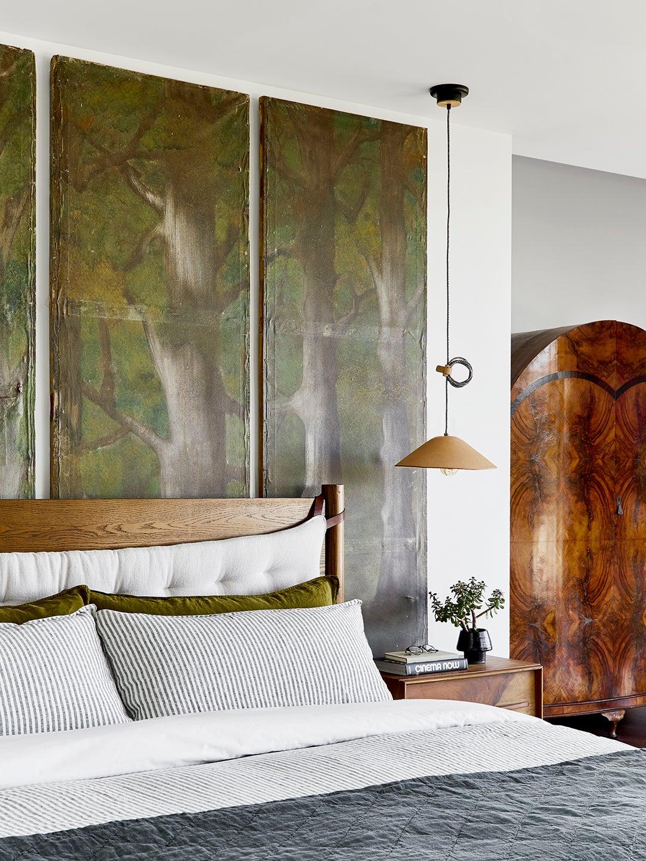 green art triptych behind bed in bedroom