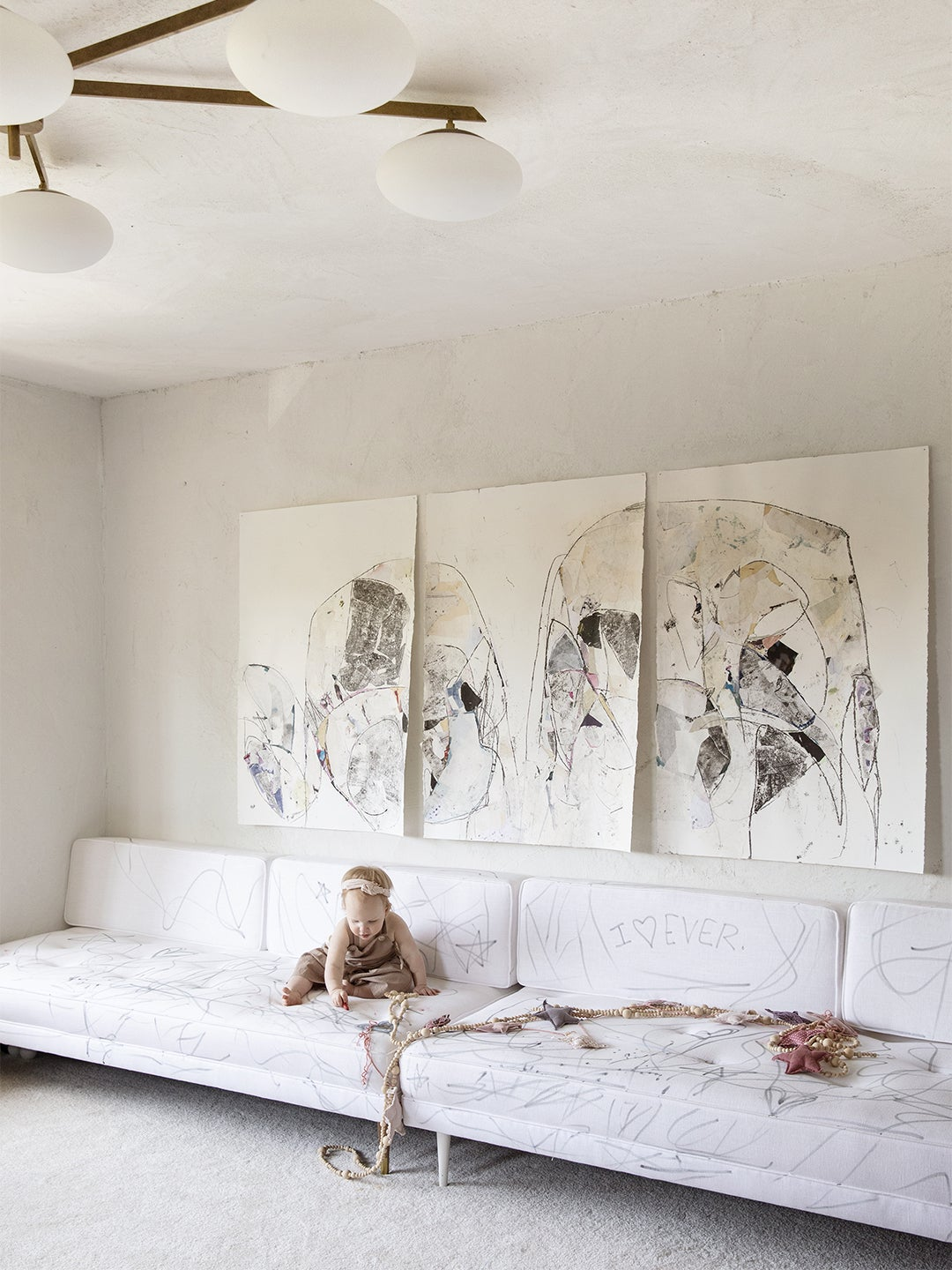 white room with baby on a white sofa